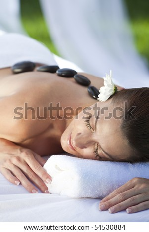 A woman relaxing at a health spa while having a hot stone treatment or massage