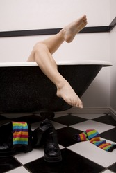 A woman relaxing in her tub after throwing her colorful striped socks off.