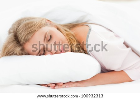 A woman resting in bed with her head on the pillow and her hands underneath it and her eyes are closed.