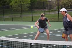 A woman returns a pickleball shot during a women's doubles match