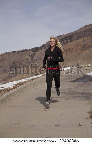 A woman running down a road with a smile on her face.