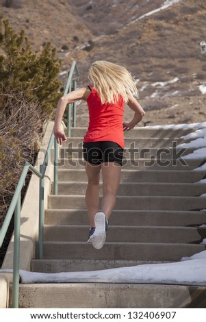 A woman running up the stairs in the outdoors with snow all around her.