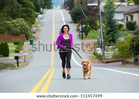 A woman runs with her golden retriever dog on the street