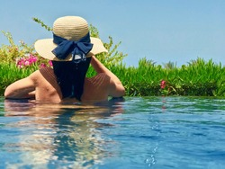 A woman's back wearing a straw hat with ribbon in a pool, water, with greenery in the background.