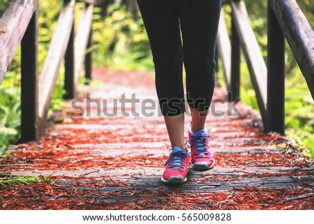 Shutterstock A woman's feet as she walks across a bridge in a green forest