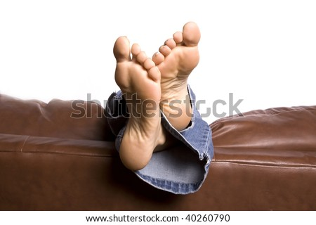 A woman's feet relaxing and hanging over the back of the brown couch with ankles crossed.