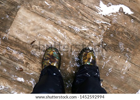 A woman's feet, wearing waterproof rain boots are standing in a flooded house with vinyl wood floors. Stock photo ©