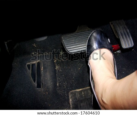 A woman's foot depressing the brake pedal of a sportscar.