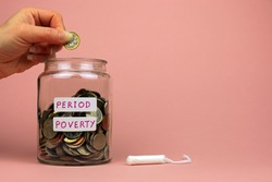A Woman's Hand Adding A Pound Coin To A Glass Jar. Period Poverty Concept.