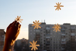 A woman's hand draws snowflakes on the window with paint, everything is illuminated by a soft yellow sunset light, close-up, copy space. Preparing for Christmas and New Year, home decoration