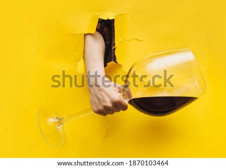 A woman's hand emerges through a torn hole in yellow paper with a large glass of red wine. The concept of alcoholism, drunkenness and hangover.