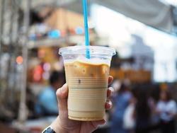 A woman's hand holding plastic glass of iced coffee latte; upper layer is brown bitter coffee lower is fresh milk, blur background with selective focus.