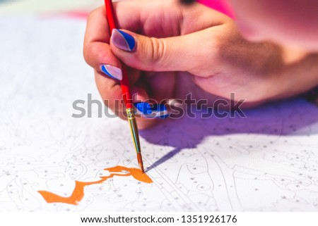 A woman's hand holds a brush and draws a picture by numbers. Drawing on canvas. Numbered paint cans. Number coloring page. Novice artist. Art idea. Closeup, selective focus.  #1351926176