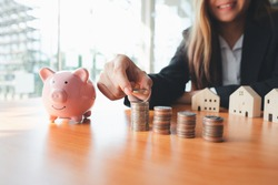 A woman's hand holds a coin to manage money and Plan your savings to buy the best home for your family, ideas for savings, growth, economy, business and investing.