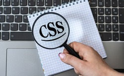 A woman's hand holds a magnifying glass over the word CSS (Cascading Style Sheets) against the background of a laptop. Internet concept