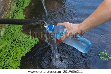 A woman's hand holds a plastic bottle and pours water from a nat Photo stock ©