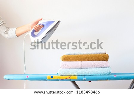A woman's hand holds an iron over a pile of clean ironed towels on the ironing board. Homework Concept #1185498466