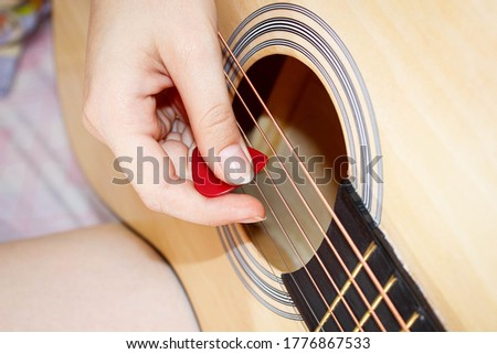 A woman's hand plays a guitar pick on the strings. Close-up, selective shot. stock photo