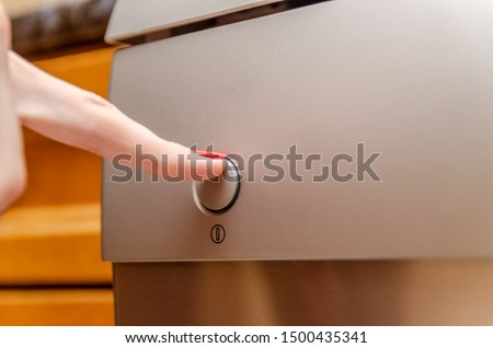 A woman's hand presses the switch on the dishwasher close-up #1500435341