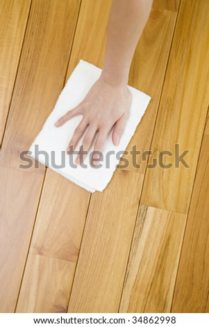 A woman's hand sweeping a wooden floor