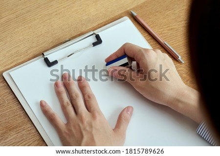 A woman's hand that erases the letters on the document with an eraser ストックフォト ©