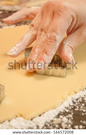 A woman\'s hand using a metal cookie cutter to cut shapes out of rolled out dough.
