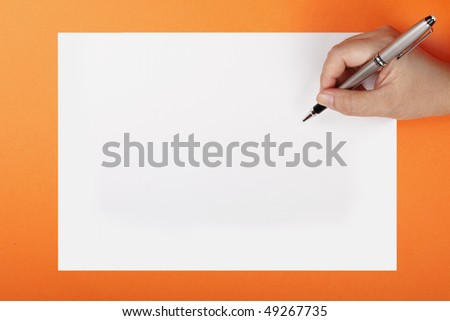 A woman's hand with a pen on a piece of paper