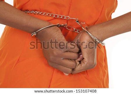 A woman's handcuffs in her orange prison outfit