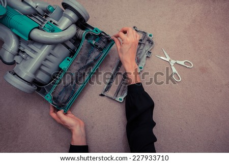 A woman\'s hands are cleaning and repairing a vacuum cleaner