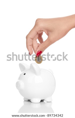 A woman's manicured hand dropping a coin into a  piggy bank isolated on white.