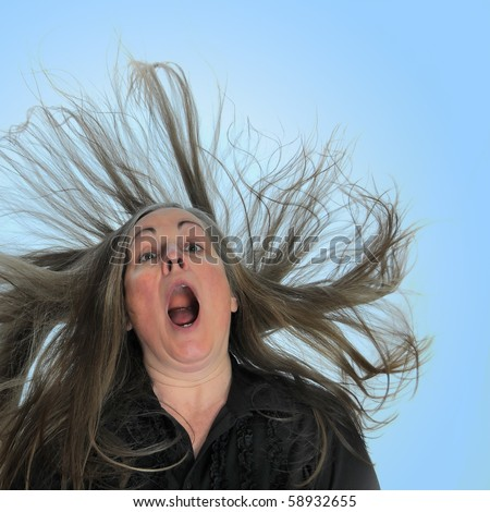 A woman screaming in front of a blue background with her hair blasting behind her.