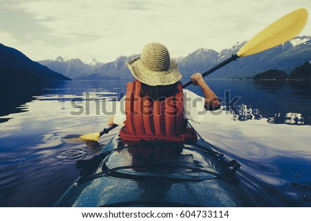 A woman sea kayaking on the flat calm water of Muir Inlet in Glacier Bay National Park #604733114