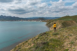 A woman sea shore back in a bright yellow jacket. A lonely person stands on the shore and enjoys the views of the city and the sea bay. Autumn landscape with clouds, cloudy day Koktebel Crimea