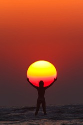 A woman seems to hold the sun in her hands on the sunset in India, Maharashtra, Paradise Beach.