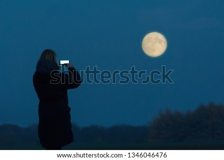 A woman seen as silhouette takes a picture of the full moon with her cell phone