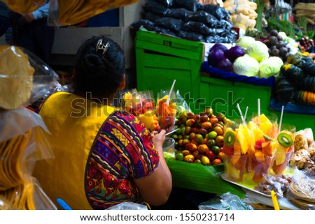 A woman sells fruits in the Zunil Guatemala town market.
