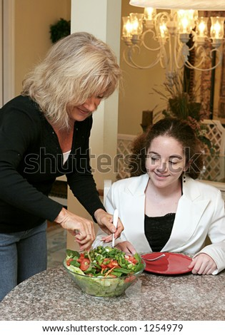 A woman serving a healthy tossed salad to a friend.