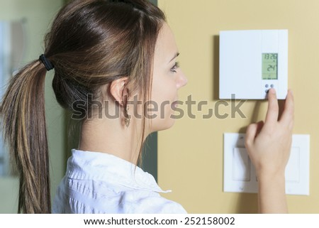 A woman set the thermostat at house. Foto stock ©