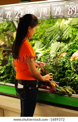 A woman shopping at produce section of grocery store