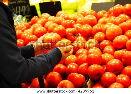A woman shopping for tomatoes at the supermarket