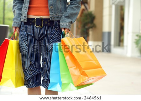 A woman shopping in a mall carrying shopping bags
