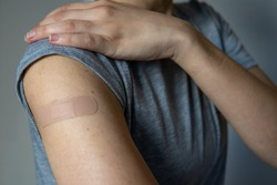 A woman showing her arm with an adhesive bandage after injection of vaccine or a scratch on the skin. First aid. Medical, pharmacy, and healthcare concept. After vaccination treatment.