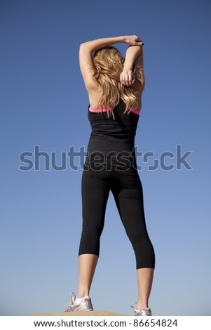 a woman showing the back view of her while she is stretching her arm.