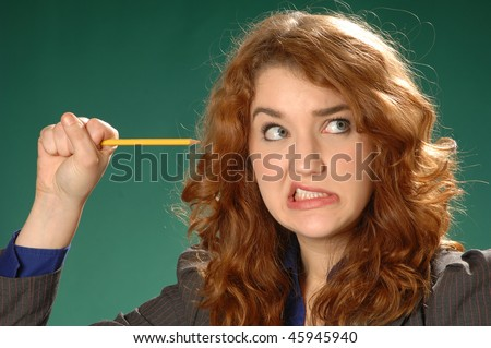 a woman shows a face and grips a pencil in frustration