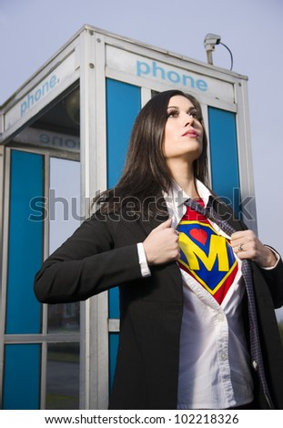 A Woman shows her Super Mother Uniform underneath her street clothes outside a phone booth emerging Superhero