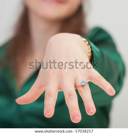 A woman shows off her new ring with blue gem