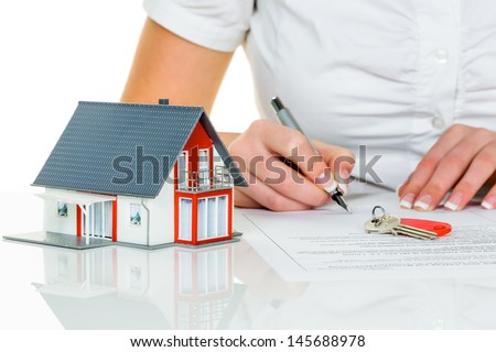 a woman signs a purchase contract for a home with a real estate agent. - stock photo