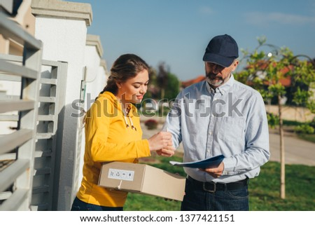 A woman signs for wrongly delivered post #1377421151
