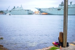 A woman siting on the beach and Battleship in the background.