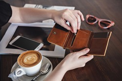 A woman sits at a table in a cafe and takes out a credit card from her wallet to pay for coffee. Close-up, no face, copy space, horizontal orientation.